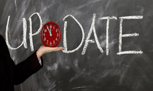"Image: hand with clock in front of ""Update"" written on blackboard"